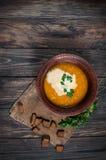 碗南瓜汤用在木桌上的面包油煎方型小面包片 免版税库存照片