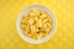 碗反对织地不很细背景的水多的菠萝 图库摄影