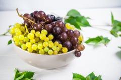 碗各种各样的葡萄:红色,白色和黑莓果和绿色叶子在白色木桌上 选择聚焦 复制空间 免版税图库摄影