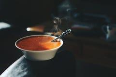 碗在一个皮革沙发的胳膊的蕃茄汤 库存照片