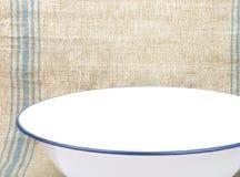 碗在亚麻制板料的搪瓷 库存照片
