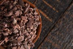 碗在土气木表上的未加工的巧克力鸟嘴 库存照片