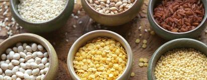 碗在小容器的各种各样的谷物在木背景,谷物混合,豆,芝麻,米,大麦米,麦子,特写镜头 免版税库存照片