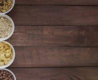 碗在木背景的各种各样的谷物与您的空间 库存照片
