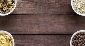 碗在木背景的各种各样的谷物与空间 图库摄影