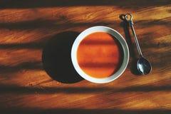 碗在橡木桌上的蕃茄汤与阴影 免版税库存图片