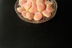 碗在水晶刻花玻璃盘的加糖的果冻甜点在最小的金属黑背景 库存图片