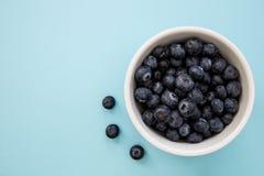 碗在蓝色背景的蓝莓与拷贝空间 库存图片