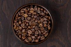 碗在黑暗的背景,顶视图的咖啡豆 免版税库存图片
