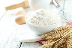 碗小麦面粉用鸡蛋和在白色木backgrou扫 免版税库存照片