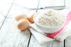 碗小麦面粉用鸡蛋和在白色木backgrou扫 库存图片