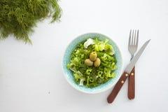 碗新鲜的叶茂盛蔬菜沙拉用橄榄、莳萝、葱和辣椒粉 库存图片