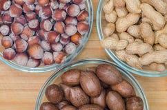 碗未加工的榛子和山核桃果在木背景 产油 免版税库存图片