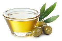 碗橄榄油和绿橄榄与叶子 免版税库存图片