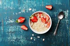 碗燕麦粥粥用草莓和杏仁在葡萄酒小野鸭在舱内甲板位置样式的台式视图剥落 健康的早餐 库存照片