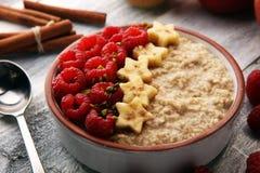 碗燕麦粥粥用香蕉、莓椰子和在土气桌,热和健康食品上的焦糖调味汁早餐 库存图片