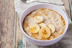碗燕麦粥粥用香蕉和焦糖在土气桌,热和健康早餐调味 库存图片