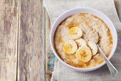 碗燕麦粥粥用香蕉和焦糖在土气桌,热和健康早餐调味 免版税库存图片