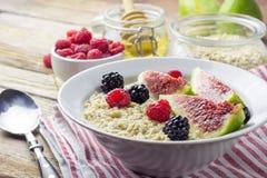 碗燕麦粥粥用香蕉,蓝莓、杏仁、椰子和焦糖在小野鸭土气桌,热和健康食物f调味 免版税图库摄影
