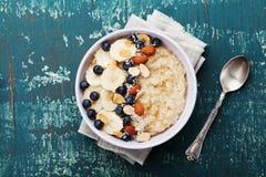碗燕麦粥粥用香蕉,蓝莓、杏仁、椰子和焦糖在小野鸭土气桌,顶视图,舱内甲板位置上调味 免版税库存图片