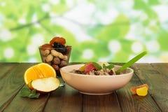 碗燕麦粥,与坚果的玻璃,烘干了在抽象绿色的果子 免版税库存图片