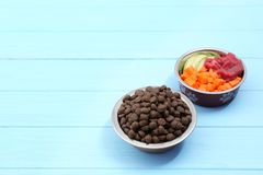 碗用在木背景的干和自然狗食 免版税库存图片