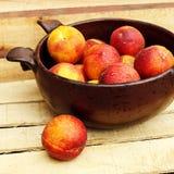 碗用在木背景的新鲜的桃子 免版税库存照片