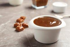 碗用在灰色桌上的鲜美焦糖调味汁 免版税库存图片