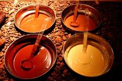 碗用在褐色的五颜六色的熔化巧克力烤了可可子背景 乳状,黑,白色和棕色巧克力 免版税图库摄影