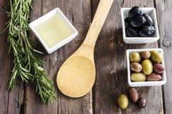 碗用新鲜的橄榄、橄榄油和草本填装了 免版税库存图片