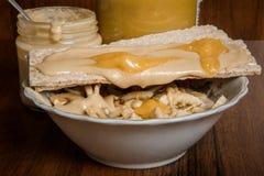 碗用燕麦粥和黑麦大面包冠上与tahini和蜂蜜 免版税库存图片