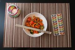 碗用米、菜和筷子在竹Placemat 免版税库存图片