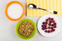 碗用酸奶, muesli,板材用樱桃,在餐巾的匙子 免版税库存图片