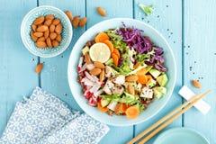 碗用鲕梨、萝卜、圆白菜无头甘蓝、红萝卜和莴苣叶子烤鸡肉、糙米和新鲜蔬菜沙拉  免版税图库摄影