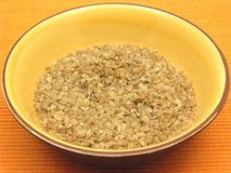 碗碾碎干小麦陶瓷少量麦子 图库摄影