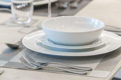 碗筷和餐巾在桌上 库存图片