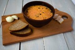 碗红色汤面包葱在船上 免版税库存照片