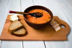 碗红色汤面包葱在船上 免版税库存图片