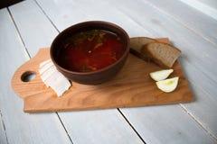 碗红色汤面包葱在船上 库存照片