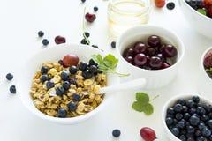 碗自创格兰诺拉麦片用草莓、蓝莓、樱桃、鹅莓、黑醋栗和蜂蜜在白色木背景 免版税图库摄影