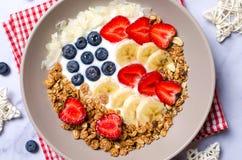 碗自创格兰诺拉麦片用酸奶和新鲜的莓果以美国旗子,可口健康早餐的形式 免版税库存照片