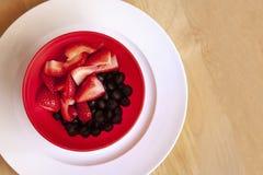碗草莓和蓝莓在一块白色板材 库存照片
