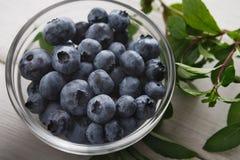 碗蓝莓和薄荷的棍子在土气木头 库存照片