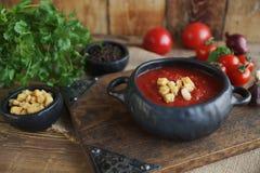 碗蕃茄汤用荷兰芹、丁香和黑胡椒在葡萄酒板和土气木背景,选择聚焦 免版税库存图片