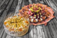碗被装饰的奥利维尔沙拉和满盘在老被风化的片状庭院表上的开胃菜美味盘集合 库存图片
