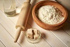 碗顶视图与酵母和滚针的面粉在白色厨房用桌上 库存图片