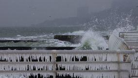 碰撞入码头栏杆的波浪盖用冰 库存图片