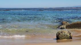 碰撞反对在海滩的小岩石的波浪与在左边的空间 影视素材