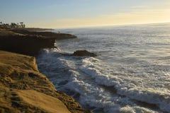 碰撞反对日落峭壁的波浪 免版税库存照片