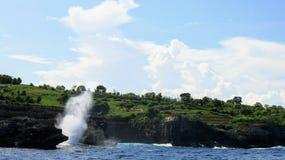 碰撞反对珀尼达岛海岛岩石海岸峭壁的海波浪在印度尼西亚 免版税库存图片